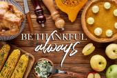 vrchní pohled na pečeného krocana, dýňový koláč a grilovanou zeleninu servírovanou na dřevěném stole s vděčností vždy ilustrující