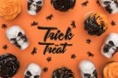 felső kilátás ízletes Halloween cupcakes pókok és koponyák narancs alapon trükk vagy élvezet illusztráció