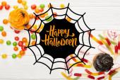 felső nézet színes gumi édességek, cupcakes és bonbons fehér fa asztal pókháló és boldog Halloween illusztráció