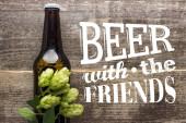 Draufsicht auf frisches Bier in Flasche mit grünem Hopfen auf Holzoberfläche mit Bier mit dem Freunde-Schriftzug