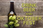 Draufsicht auf frisches Bier in Flasche mit grünem Hopfen auf Holzoberfläche mit Trinkbier und Oktoberfest-Schriftzug
