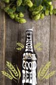 vrchní pohled na čerstvé pivo v láhvi s dobrými lidmi pít dobré pivo nápisy v blízkosti zeleného chmele na dřevěném povrchu