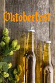 vrchní pohled na čerstvé pivo v lahvích se zeleným chmelem na dřevěném povrchu s nápisem Oktoberfest