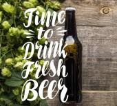 Draufsicht auf frisches Bier in Flasche mit grünem Hopfen auf Holzoberfläche mit Zeit, frisches Bier zu trinken Illustration