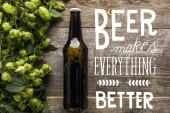 Fotografie Draufsicht auf frisches Bier in Flasche mit grünem Hopfen auf Holzoberfläche mit weißem Bier macht alles besser Illustration