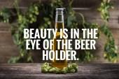 Frisches Bier in Flasche mit grünem Hopfen auf hölzerner Oberfläche mit Schönheit liegt im Auge des Bierhalters Illustration