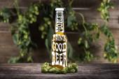 Frisches Bier in der Flasche mit guten Leuten trinken gutes Bier Schriftzug in der Nähe von grünem Hopfen auf hölzerner Oberfläche