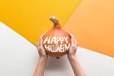cropped view of woman holding ripe pumpkin with happy Halloween illustration on white and orange background