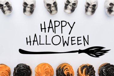 top view of delicious Halloween cupcakes and skulls on white background  with happy Halloween illustration