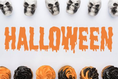 top view of delicious Halloween cupcakes and skulls on white background  with Halloween illustration
