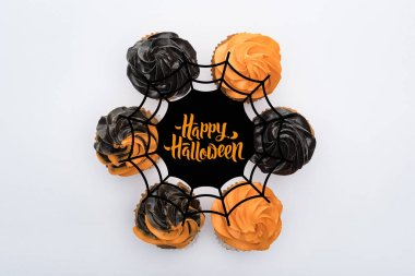 top view of delicious Halloween cupcakes in circle with spiderweb and happy Halloween illustration isolated on white