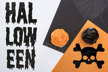 top view of delicious Halloween cupcakes on black, orange and white background with Halloween illustration