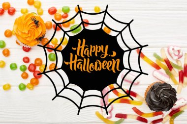top view of colorful gummy sweets, cupcakes and bonbons on white wooden table with spiderweb and happy Halloween illustration