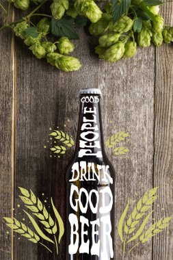 Top view of fresh beer in bottle with good people drink good beer lettering near green hop on wooden surface stock vector