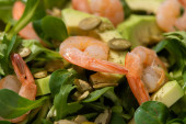 Photo close up view of fresh green salad with pumpkin seeds, shrimps and avocado