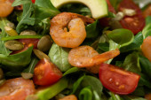 close up view of fresh green salad with pumpkin seeds, cherry tomatoes, shrimps and avocado