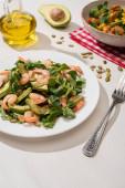 selektivní zaměření čerstvého zeleného salátu s krevetami a avokádem na talíře u vidličky a oleje