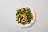 top view of fresh green salad with pumpkin seeds, shrimps and avocado on plate on white background