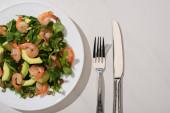 vrchní pohled na čerstvý zelený salát s dýňovými semínky, krevetami a avokádem na talíři u příborů na bílém pozadí