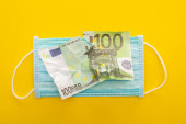top view of torn euro banknote and medical mask on yellow background