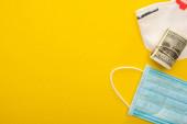 Draufsicht auf Geldrolle, Sicherheits- und medizinische Masken auf gelbem Hintergrund