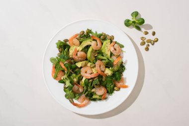 Top view of fresh green salad with pumpkin seeds, shrimps and avocado on plate on white background stock vector
