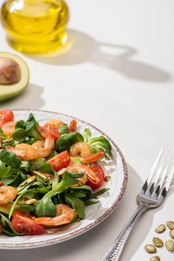 Selective focus of fresh green salad with shrimps and avocado on plate near fork and ingredients on white background stock vector