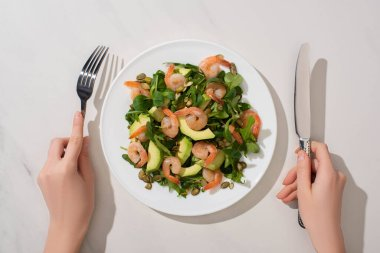 Partial view of woman eating fresh green salad with pumpkin seeds, shrimps and avocado on white background stock vector