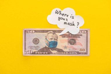 KYIV, UKRAINE - 25 Mart 2020: Sarı arka planda tıbbi maske ve konuşma baloncuğu çizilmiş dolar banknotunun üst görüntüsü