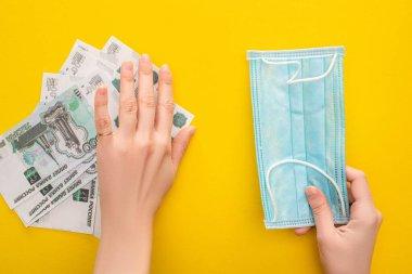 KYIV, UKRAINE - 25 Mart 2020: Rus banknotlarını kenara koyan ve sarı arka planda tıbbi maske tutan kadının kısmi görüntüsü