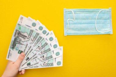 KYIV, UKRAINE - 25 Mart 2020: Sarı arka planda Rus banknotları tutan kadının kısmi görüntüsü