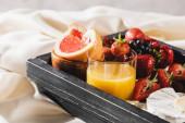 zblízka pohled na francouzskou snídani s grapefruitem, camembert, pomerančový džus, bobule na dřevěném podnosu