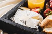 zblízka pohled na francouzskou snídani s camembert, pomerančový džus, jahody a bageta na dřevěném podnosu
