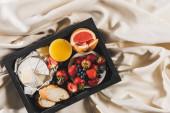 horní pohled na francouzskou snídani s grapefruitem, camembert, pomerančový džus, bobule a bageta na podnose na bílém ubrusu