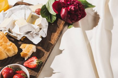 French breakfast with strawberries, croissant, Camembert, peony on wooden cutting board on white tablecloth stock vector