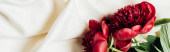 Photo top view of red peonies on white cloth, panoramic shot