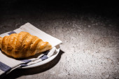 fresh baked croissant on towel and plate on concrete grey surface in dark