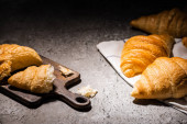 fresh baked croissants on towel near cutting board on concrete grey surface in dark