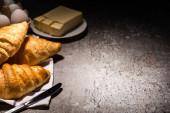 szelektív fókusz a friss sült croissant késsel törölközőn közel vaj és tojás beton szürke felületen sötét