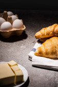 selective focus of fresh baked croissants on towel near butter and eggs on concrete grey surface in dark