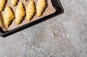 pohled shora na nevařené croissanty na tácu na betonovém šedém povrchu