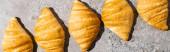 lapos feküdt friss sült croissant beton szürke felületen, panorámás lövés