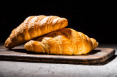 fresh baked croissants on wooden cutting board on concrete grey surface isolated on black