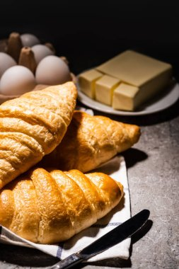 Selective focus of fresh baked croissants with knife on towel near butter and eggs on concrete grey surface in dark stock vector