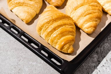 Baked delicious croissants on baking tray on concrete grey surface stock vector