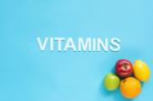 Fotografie horní pohled na zralé ovoce a slovo vitamíny na modrém pozadí