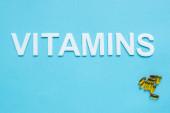Ansicht von Pillen und Word-Vitaminen auf blauem Hintergrund