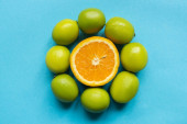 top view of ripe orange and limes arranged in circle on blue background