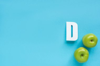 Top view of ripe green apples and letter D on blue background stock vector
