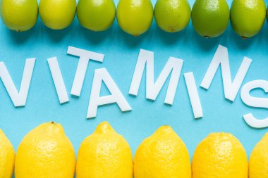 Top view of ripe yellow lemons and limes on blue background with word vitamins stock vector